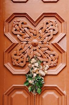 Drewniane drzwi z ręcznie robionym wzorem. bukiet gałązek dębowych i oliwek to symbol wigilii w serbii, czarnogórze, bośni i chorwacji