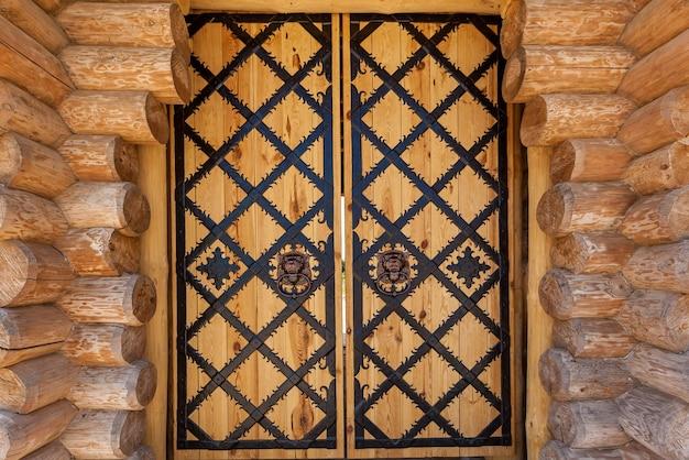 Drewniane drzwi z żelaznym kuciem. antyczne drewniane antyczne drewniane drzwi z kutą kratą żelaza i poprzeczkami na białym tle na białym tle.