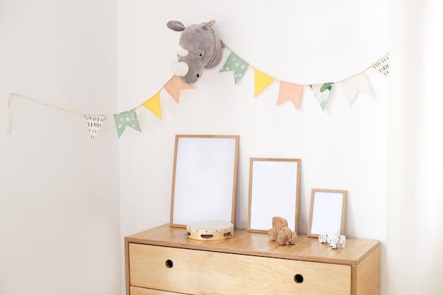 Drewniane ekologiczne zabawki dla dzieci, ramki drewniana komoda i biała ściana z flagami wakacyjnymi, wnętrze sypialni dla dzieci. biała ściana ozdobiona flagami w przedszkolu
