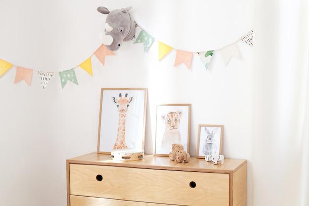 Drewniane ekologiczne zabawki w pokoju dziecięcym, plakaty, ramki drewniana komoda i biała ściana z flagami świątecznymi, wnętrze sypialni dziecięcej. biała ściana ozdobiona flagami w przedszkolu