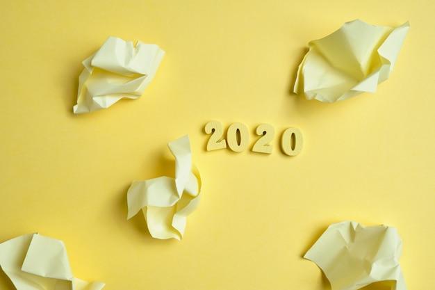 Drewniane figurki 2020 obok zmiętych naklejek na żółtym tle. widok z góry.