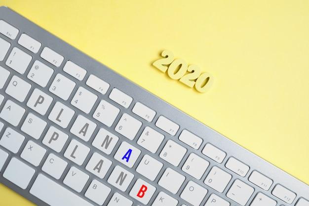 Drewniane figurki 2020 z klawiaturą z napisem plan a i plan b na żółtym tle.