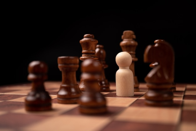 Drewniane figurki (biznesmen) stojące przed królem szachowym i będące w kręgu szachowym.