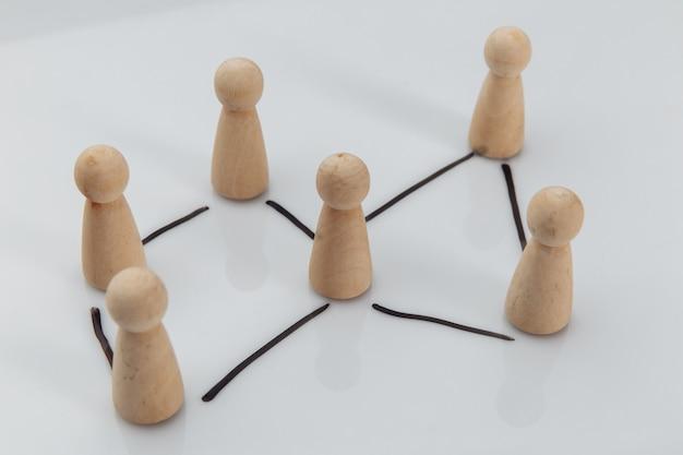 Drewniane figurki jako symbol drużyny na białym stole. zasoby ludzkie i koncepcja zarządzania.