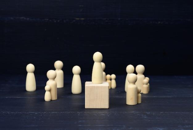 Drewniane figurki mężczyzn na niebieskiej powierzchni
