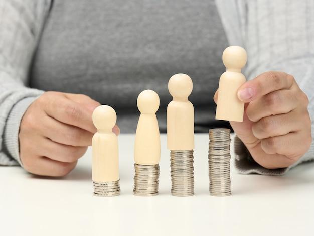 Drewniane figurki mężczyzn stoją na stosach monet, biały stół. mentoring pracowniczy i koncepcja rozwoju, wzrost dochodów i wynagrodzeń