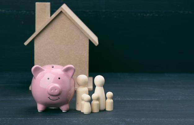 Drewniane figurki rodzinne, ceramiczna różowa skarbonka i model domku. zakup nieruchomości, koncepcja wynajmu. przeprowadzka do nowych mieszkań, skopiuj przestrzeń