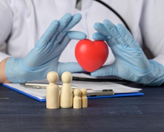 Drewniane figurki rodziny i czerwone serce w rękach lekarza. pojęcie rodzinne ubezpieczenie zdrowotne, z bliska