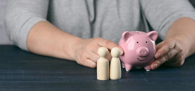 Drewniane figurki rodziny małych mężczyzn na powierzchni mężczyzny ze skarbonką. pojęcie oszczędności i długoterminowego budżetowania, oszczędności kosztów. zwrot pieniędzy z zakupów, korzyść