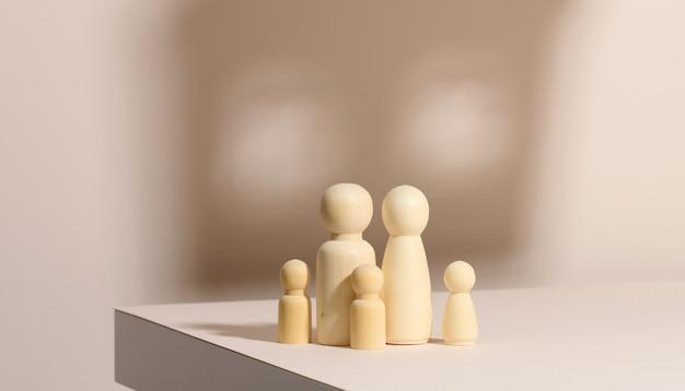 Drewniane figurki rodziny na tle cienia w formie domu. beżowe tło. domowe marzenia, kredyt hipoteczny