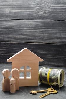 Drewniane figurki rodziny stoją w pobliżu drewnianego domu z kluczami.