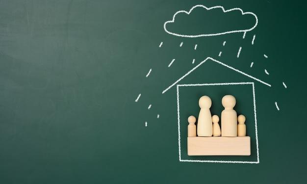 Drewniane figurki rodziny w domu narysowane białą kredą i deszczem z chmury. nieruchomość