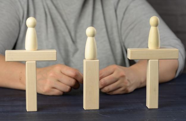Drewniane figurki stoją na moście z przeciwległych stron, koncepcja znalezienia kompromisu, konstruktywny dialog, przeciwnicy biznesu business