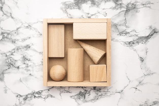 Drewniane figurki w pudełku na tle marmuru. streszczenie tło obiektów drewnianych. kompozycja geometryczna. scena z formami geometrycznymi widok z góry