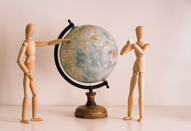 Drewniane figurki wybierające cel podróży na mapie świata. podróżuj styl życia, chwile szczęścia