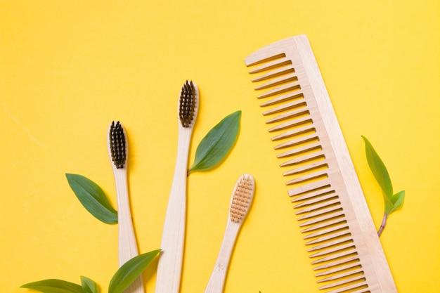 Drewniane grzebienie i bambusowe szczoteczki do zębów na żółtym tle
