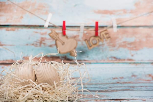 Drewniane jaja w gnieździe z napisem serca i miłości na liny
