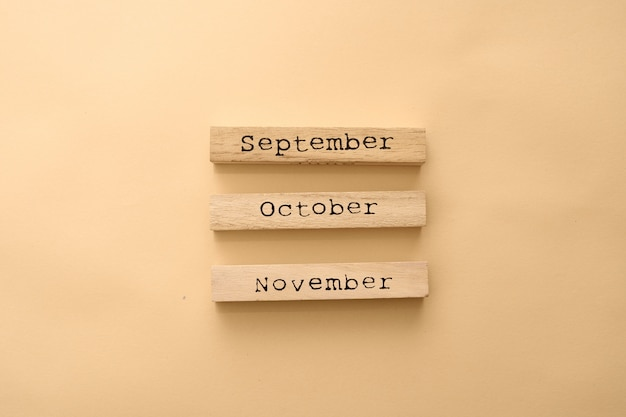 Drewniane kalendarzowe miesiące jesienne na drewnianych kostkach.