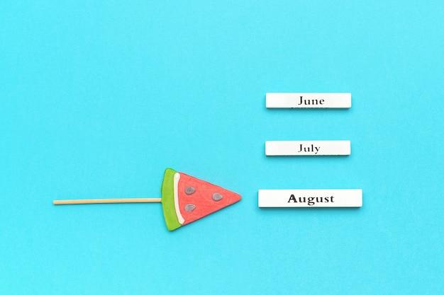 Drewniane kalendarzowe miesiące letnie sierpień, czerwiec, lipiec i lizak arbuza na patyku na niebiesko