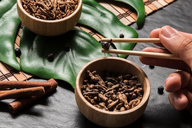 Drewniane kije trzymające chrupiącą robakę