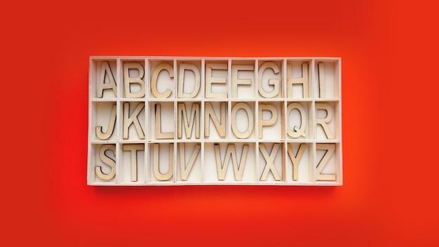 Drewniane klocki alfabetu z literami - pudełko na czerwonym tle. koncepcja nauki języka angielskiego