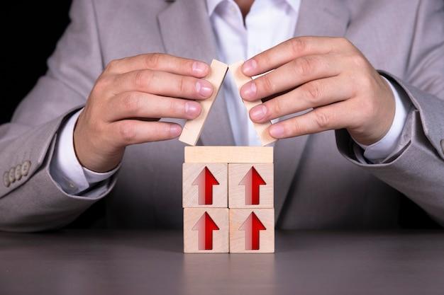 Drewniane klocki w formie domku z czerwonymi strzałkami skierowanymi w górę.