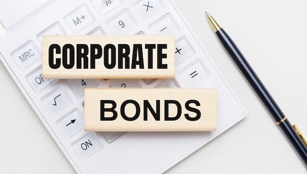 Drewniane klocki z napisem corporate bonds leżą na jasnym tle na białym kalkulatorze. w pobliżu znajduje się czarny uchwyt. pomysł na biznes