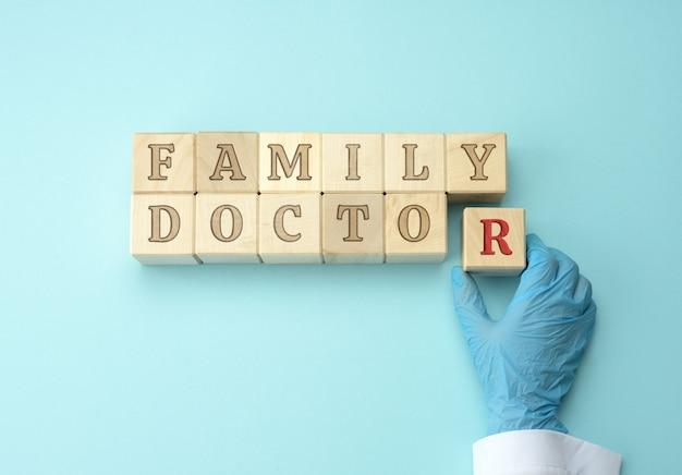 Drewniane klocki z napisem family doctor i ręką lekarza w niebieskiej lateksowej rękawiczce. koncepcja podpisania oświadczenia lekarskiego, ubezpieczenia