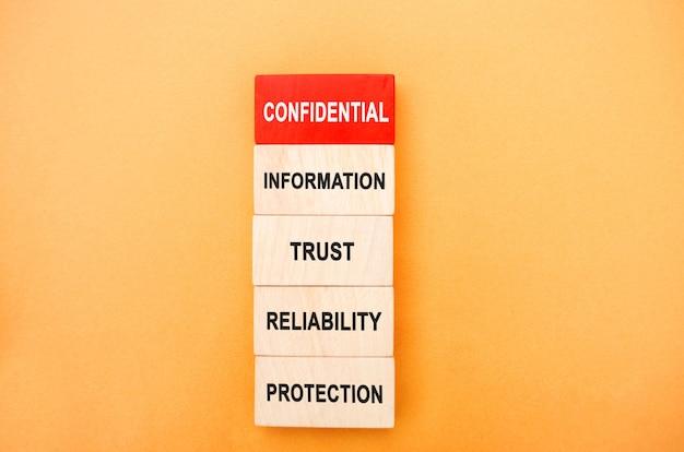 Drewniane klocki z napisem informacje poufne zaufanie niezawodność ochrona niepubliczne