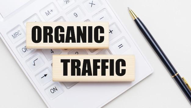 Drewniane klocki z napisem organic traffic leżą na jasnym tle na białym kalkulatorze. w pobliżu znajduje się czarny uchwyt. pomysł na biznes