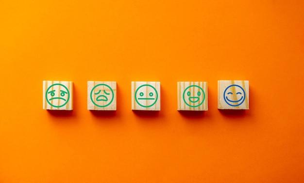 Drewniane klocki z radosnym uśmiechem na twarzy symbolu symbolu znaku na niebieskim tle, ocena, podniesienie oceny, wrażenia klienta, zadowolenie i koncepcja najwyższej jakości oceny usług