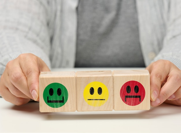 Drewniane klocki z różnymi emocjami od uśmiechu po smutek i kobiecą ręką. koncepcja oceny jakości produktu lub usługi, stanu emocjonalnego, opinii użytkowników