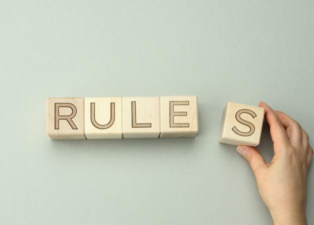 Drewniane klocki z zasadami opisów, ręka trzyma sześcian. pojęcie wyznaczania granic i warunków gry, prowadzenia biznesu, zachowań