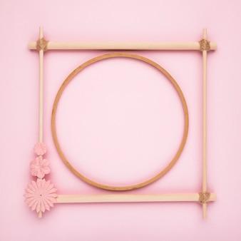 Drewniane koło wewnątrz kwadratowej ramy na różowym tle