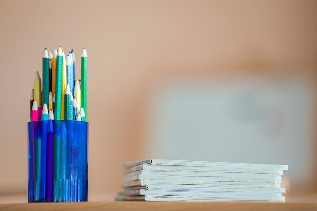 Drewniane kolorowe kredki do rysowania ułożone w plastikowy dzbanek i stos zeszytów