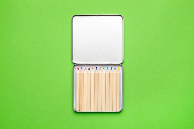 Drewniane kolorowe kredki w metalowym pudełku na zielono