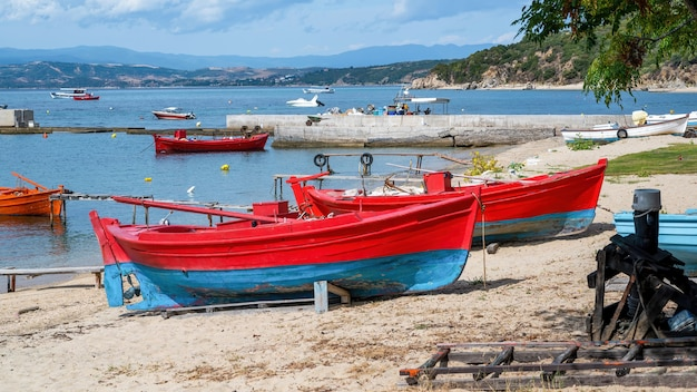 Drewniane kolorowe łodzie na plaży na wybrzeżu morza egejskiego, molo, jachty i wzgórza w ouranoupolis w grecji