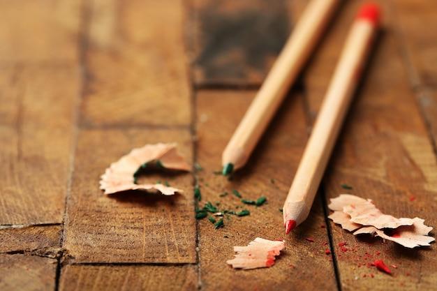 Drewniane kolorowe ołówki z ostrzącymi wiórami na drewnianym stole