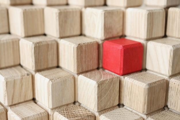 Drewniane kostki beżowego koloru w środku czerwieni stoją w piramidzie indywidualne podejście w biznesie