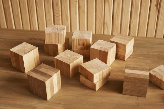 Drewniane kostki blokowe o różnych rozmiarach stoją na stole na tle drewnianej ściany