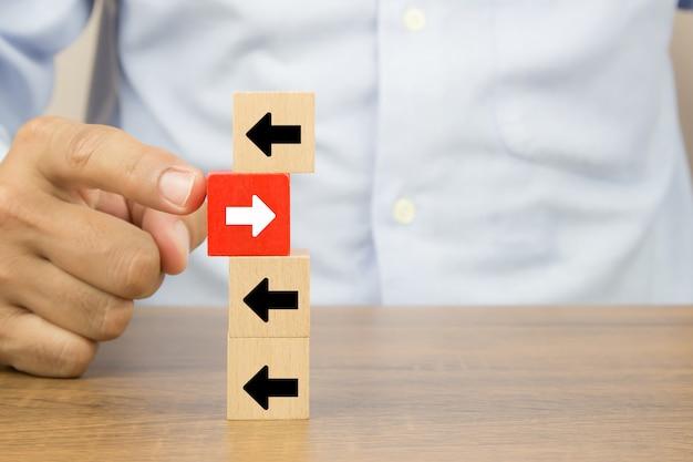 Drewniane kostki ikony grotu strzałki wskazujące przeciwne kierunki zmian biznesowych