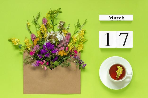 Drewniane kostki kalendarza 17 marca. puchar herbaty ziołowe, koperta kraft z wielu kolorowych kwiatów na zielonym tle