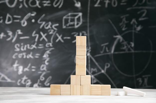 Drewniane kostki na stole z matematyką na pokładzie