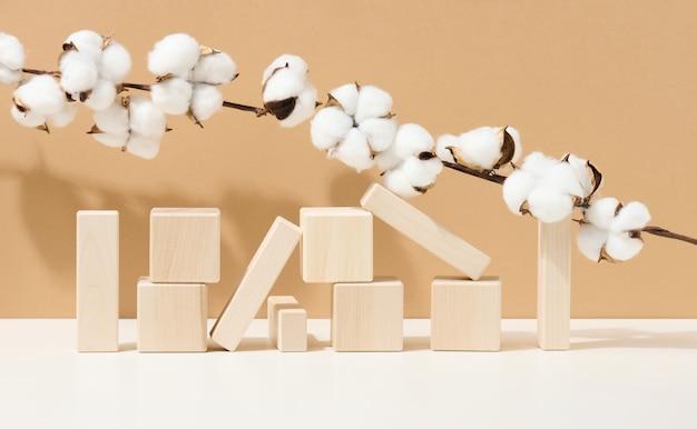 Drewniane kostki ułożone i gałęzie z białymi bawełnianymi kwiatami na brązowym tle. podium na produkty kosmetyczne, napoje i żywność, produkty ekologiczne