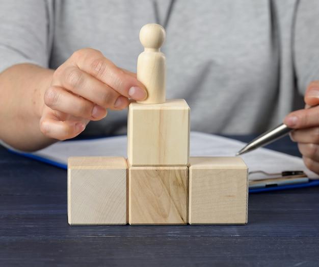 Drewniane kostki w kształcie drabiny oraz figurka mężczyzny. koncepcja rozwoju kariery, osiąganie celów. rozwój osobisty, szef korporacji, ceo