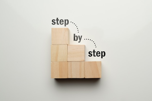Drewniane kostki w kształcie klatki schodowej z abstrakcyjną klatką schodową krok po kroku.