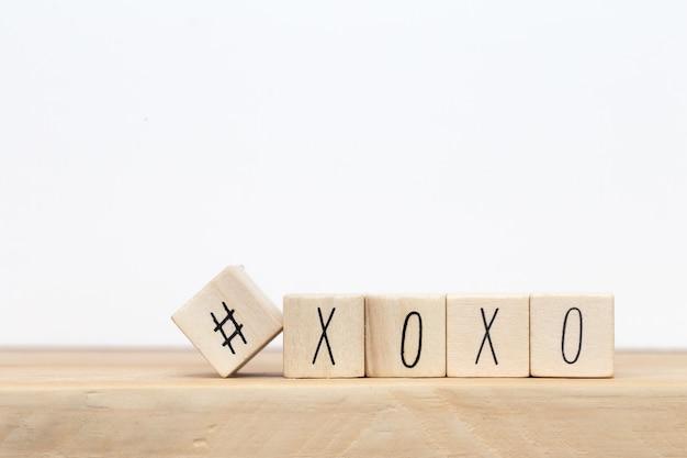 Drewniane kostki z hashtagiem i xoxo przytula i całuje listy miłosne, koncepcja mediów społecznościowych