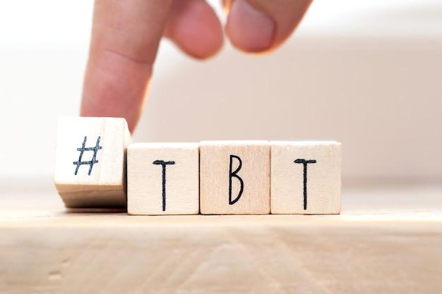 Drewniane kostki z hashtagiem tbt, co oznacza czwartek powrotny w pobliżu białego tła zbliżenia koncepcji mediów społecznościowych