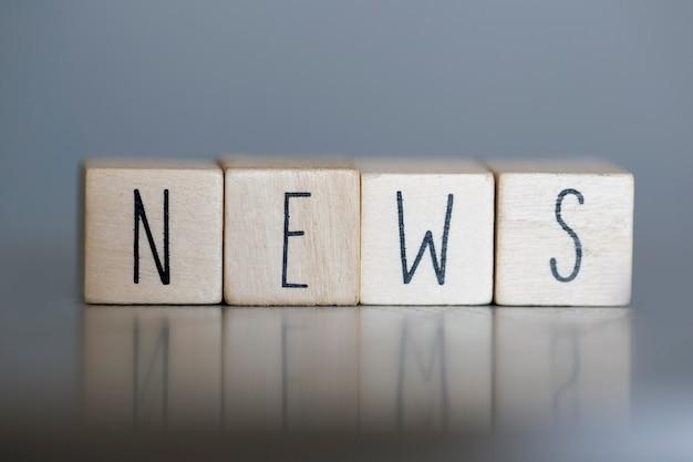 Drewniane kostki z koncepcją word news, biznesu lub mediów na szarej ścianie