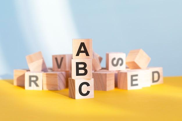 Drewniane kostki z literami abc ułożone w pionową piramidę, szare i żółte tło, koncepcja biznesowa. sla - skrót od umowy o poziomie usług